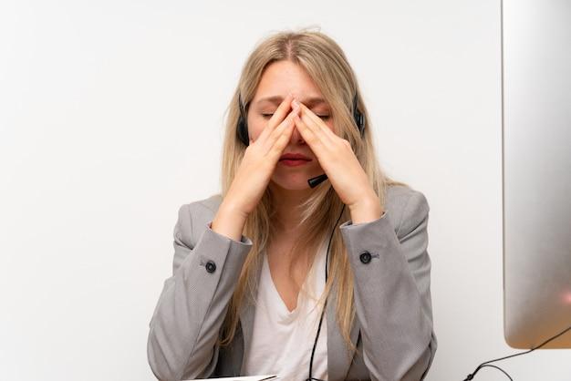 Junge frau, die mit kopfhörer in einem büro mit kopfschmerzen arbeitet
