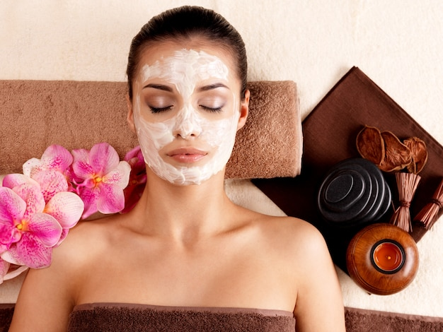Junge frau, die mit kosmetischer maske auf gesicht im schönheitssalon-innen entspannt