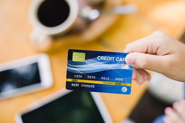 Junge frau, die mit kreditkarte für café zahlt