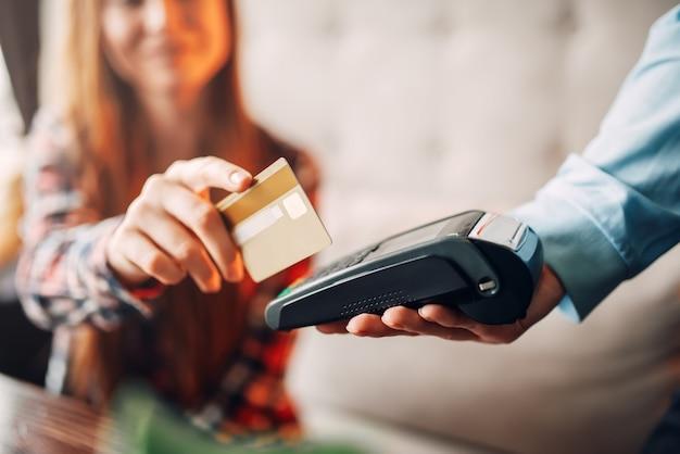 Junge frau, die mit kreditkarte im café zahlt, kellnerhand mit terminal. moderne zahlungstechnologien