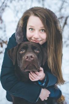 Junge frau, die mit labrador-hund im winter geht