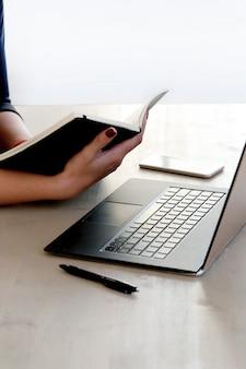 Junge frau, die mit laptop und tagesordnung arbeitet