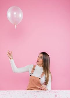 Junge frau, die mit luftballon spielt
