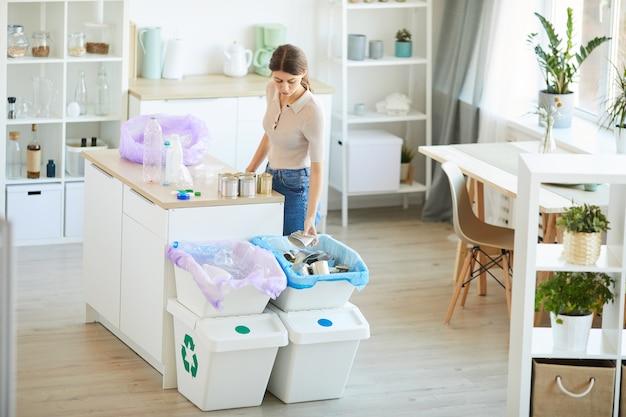 Junge frau, die mit müll arbeitet, während sie an ihrer küche steht, die den abfall trennt