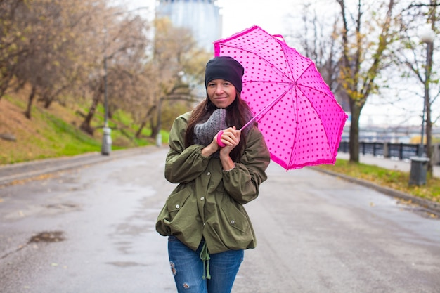 Junge frau, die mit regenschirm am regnerischen tag des herbstes geht