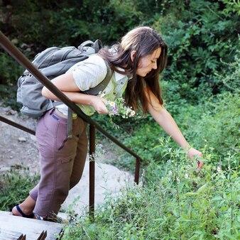 Junge frau, die mit rucksack auf den stufen auf dem waldweg wandert und wildblumen sammelt
