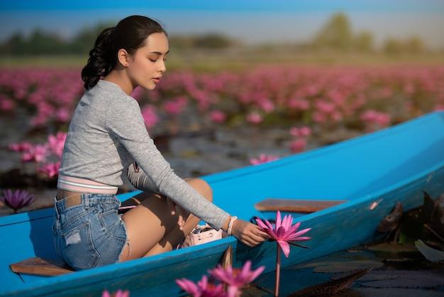 Junge frau, die mit schönem lotosblumenfeld bei red lotus sea sich entspannt