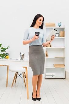 Junge frau, die mit tablette und kaffeetasse im büro steht