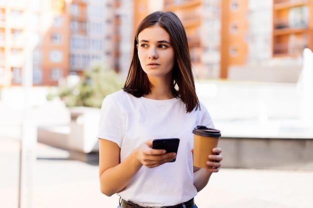 Junge frau, die mit telefon liest. weibliche frau, die nachrichten liest oder sms auf smartphone schreibt, während kaffee in der pause von der arbeit trinkt.