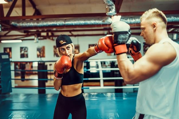 Junge frau, die mit trainer an der verpacken- und selbstverteidigungslektion trainiert