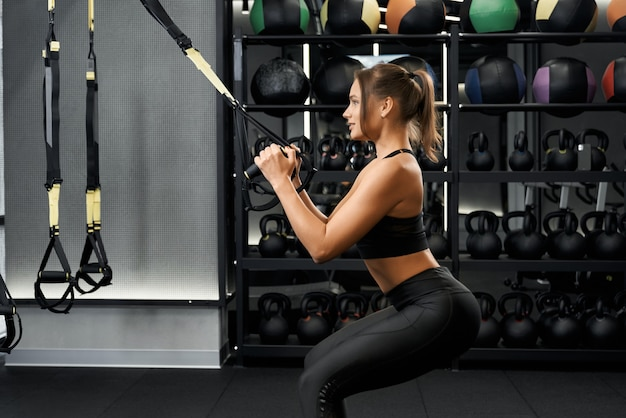 Junge frau, die mit trx im fitnessstudio arbeitet