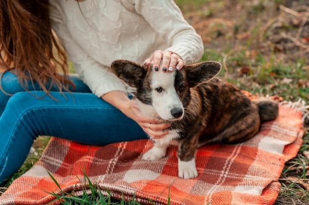 Junge frau, die mit walisischem corgi-hund im herbstlaub sitzt