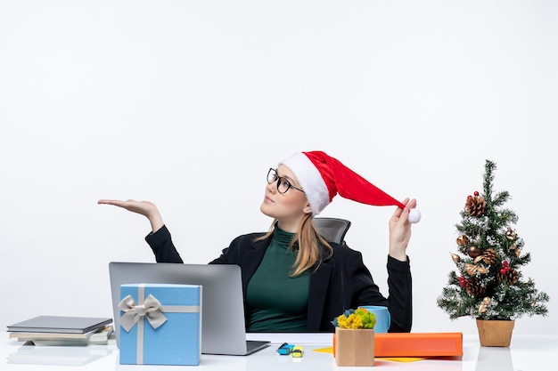 Junge frau, die mit weihnachtsmannhut und brillen spielt, die an einem tisch mit einem weihnachtsbaum und einem geschenk sitzen