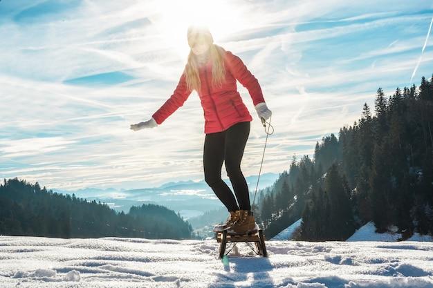 Junge frau, die mit weinleseschlittenfahren auf schneehochberg beschleunigt - glückliches mädchen, das spaß im weißen wochenurlaub hat - reisen, wintersport, ferienkonzept - hauptfokus auf ihren füßen