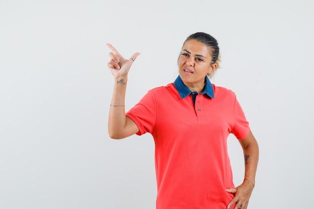 Junge frau, die mit zeigefinger nach oben zeigt und hand auf taille im roten t-shirt hält und unzufrieden aussieht. vorderansicht.