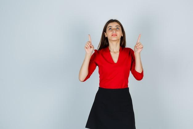 Junge frau, die mit zeigefingern in roter bluse, schwarzem rock nach oben zeigt und konzentriert schaut