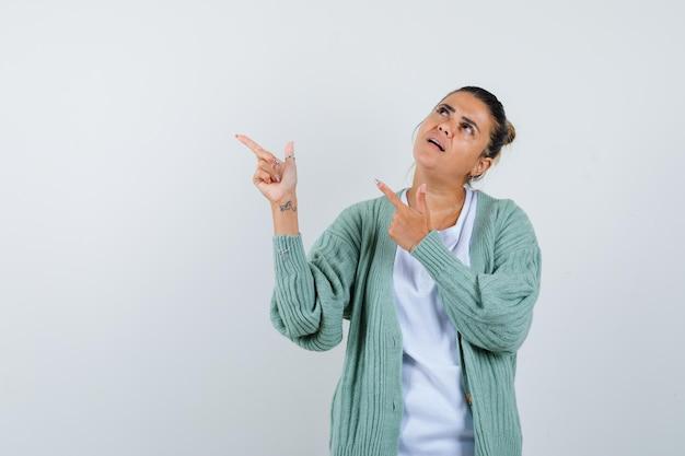 Junge frau, die mit zeigefingern in weißem hemd und mintgrüner strickjacke nach links zeigt und fokussiert aussieht looking