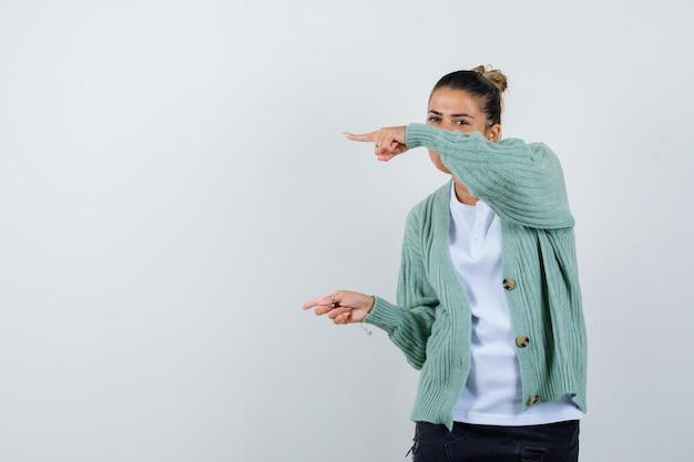 Junge frau, die mit zeigefingern in weißem t-shirt und mintgrüner strickjacke nach links zeigt und attraktiv aussieht looking