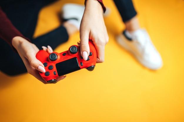Junge frau, die mit zwei gamepads auf gelb spielt.