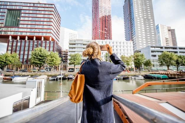 Junge frau, die moderne wolkenkratzer am hafen in der stadt rotterdam fotografiert