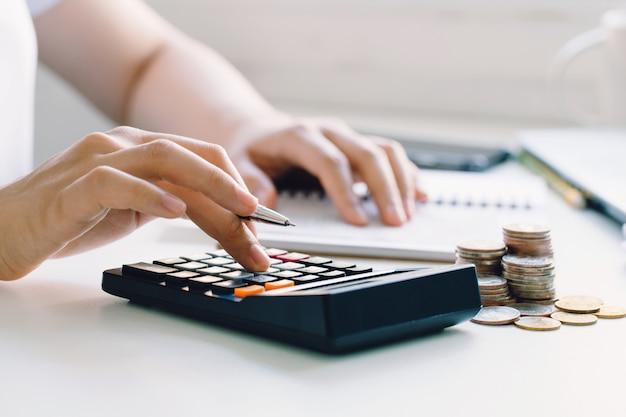 Junge frau, die monatliche hauskosten, steuern, bankguthaben und kreditkartenrechnungen berechnet. einkommenssteuer für lohnsteuern