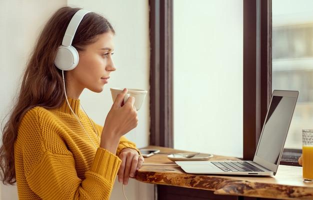 Junge frau, die morgenkaffee genießt und e-mails auf laptop prüft