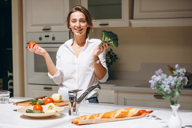 Junge frau, die morgens an der küche kocht