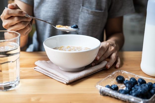 Junge frau, die morgens corn-flakes mit blueberies zu hause nährt und isst