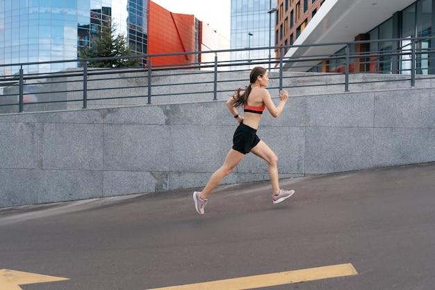 Junge frau, die morgens draußen sprintet. seitenansicht der läuferin, die in der stadt trainiert.