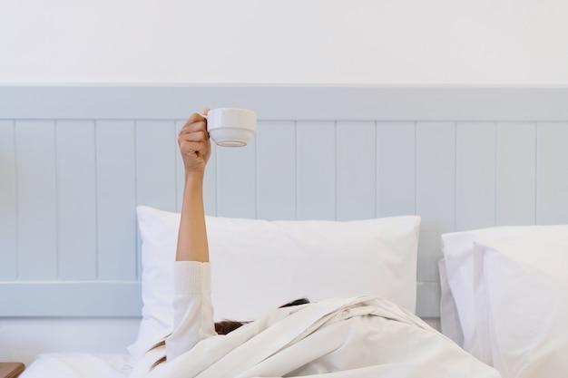 Junge frau, die morgens im bett aufwacht, sich unter der decke versteckt und mit einer tasse kaffee die arme ausstreckt.