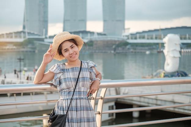 Junge frau, die morgens mit hut, glücklicher asiatischer reisenderbesuch in der singapur-stadt im stadtzentrum gelegen reist. wahrzeichen und beliebt für touristische attraktionen. asien-reisekonzept