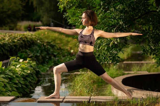 Junge frau, die morgens park des yoga, nahe einem kleinen dekorativen see tut.