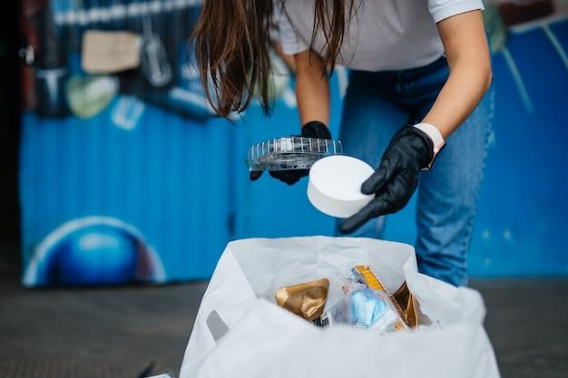 Junge frau, die müll sortiert. konzept des recyclings. kein verlust