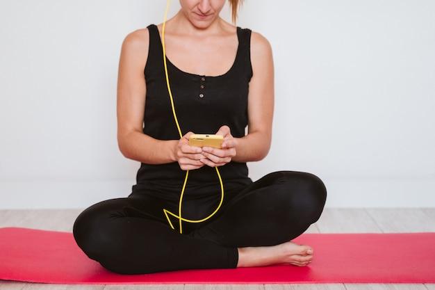 Junge frau, die musik auf gelbem handy und headset hört.