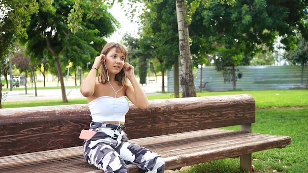 Junge frau, die musik hört, während sie auf einer bank im park sitzt