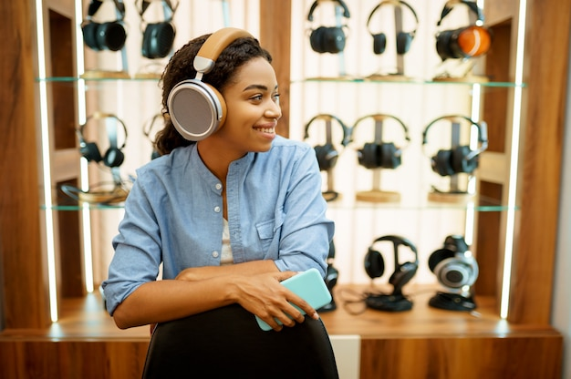 Junge frau, die musik im kopfhörerspeicher hört. weibliche person im audio-shop, schaufenster mit kopfhörern, käufer im multimedia-shop