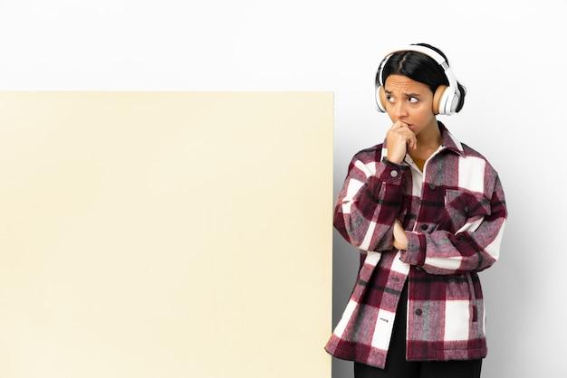 Junge frau, die musik mit einem großen leeren plakat über isoliertem hintergrund hört, der zweifel und mit verwirrendem gesichtsausdruck hat