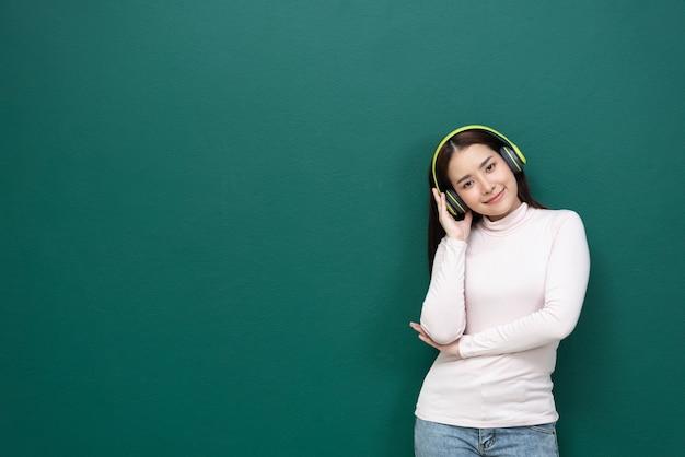 Junge frau, die musik mit kopfhörer auf grünem hintergrund hört