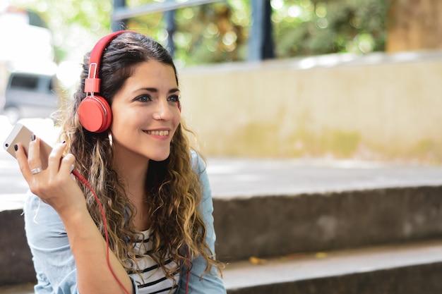 Junge frau, die musik mit kopfhörern hört.