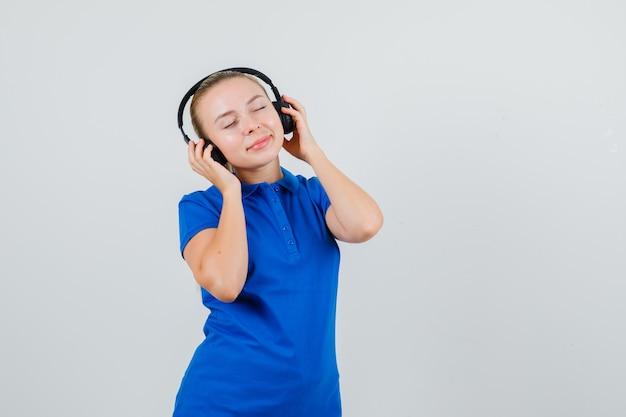 Junge frau, die musik mit kopfhörern im blauen t-shirt hört
