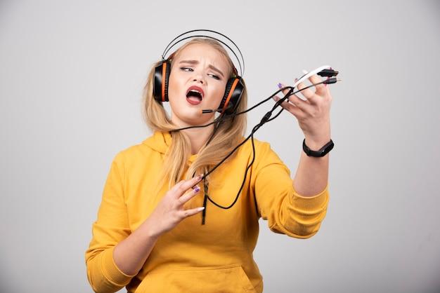 Junge frau, die musik singt und hört.
