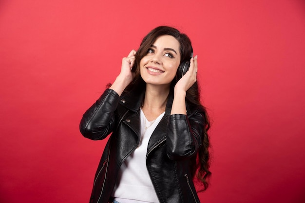 Junge frau, die musik über kopfhörer hört und auf einem roten hintergrund aufwirft. foto in hoher qualität