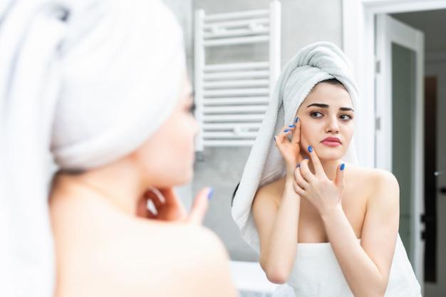 Junge frau, die nach der dusche im badezimmer auf spiegelung im spiegel schaut