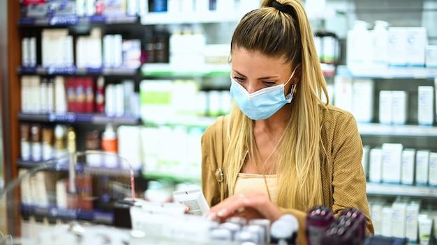 Junge frau, die nach einem produkt in einem geschäft sucht, das eine maske wegen coronavirus trägt