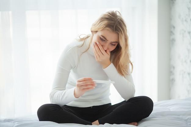 Junge frau, die nach schwangerschaftstestergebnis zu hause betrachten deprimiert und traurig sich fühlt