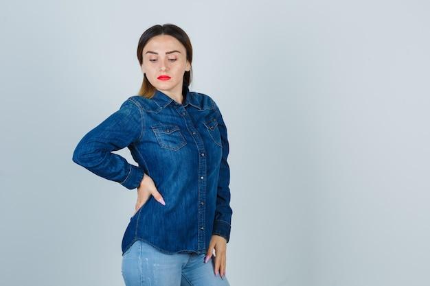 Junge frau, die nach unten schaut, während sie hand auf hüfte in jeanshemd und in jeans hält und zuversichtlich schaut