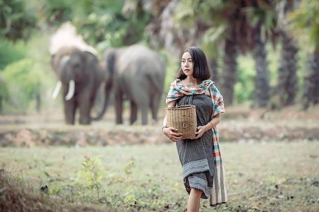 Junge frau, die nach wildem lebensmittel beim anheben ihres elefanten sucht