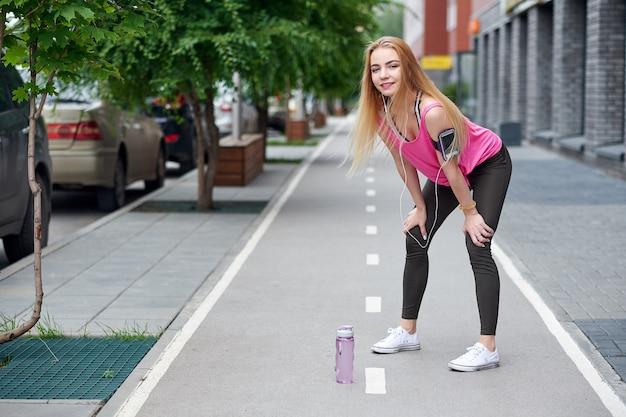 Junge frau, die nachdem dem laufen auf einem stadtweg mit einer flasche wasser stillsteht