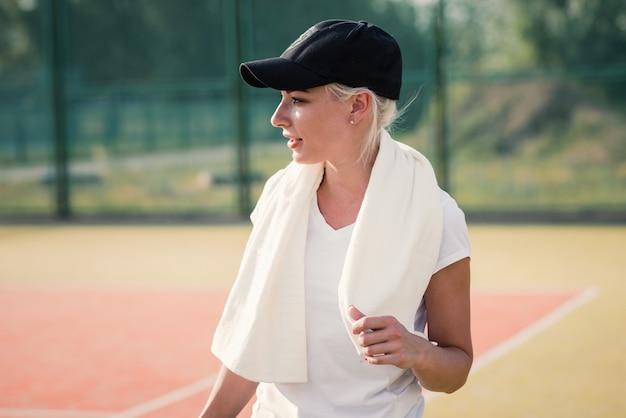 Junge frau, die nachdem sport auf tennisplatz stillsteht, getan worden ist. eignung und gesundes lebensstilkonzept