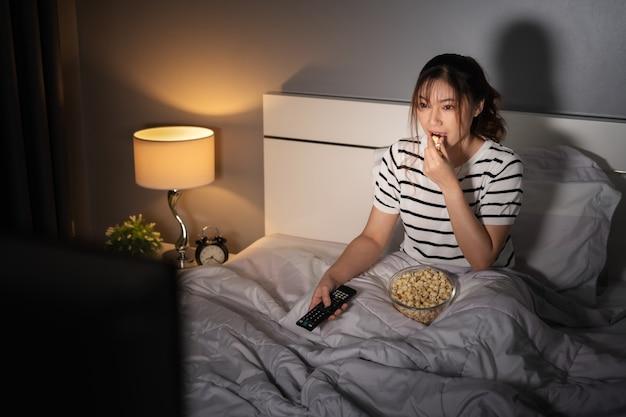 Junge frau, die nachts fernsehen sieht und popcorn auf einem bett isst